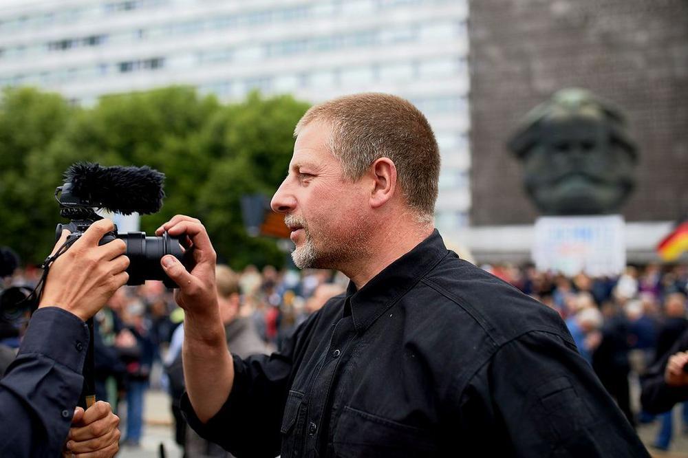 Götz Kubischek hält einem Fotografen die Hand vor das Objektiv.