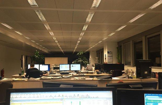 Ein Großraumbüro mit mehreren Schreibtischreihen hintereinander, an denen nur jeweils ein Mensch sitzt. Es ist draußen schon dunkel, so dass die Deckenbeleuchtung an ist.