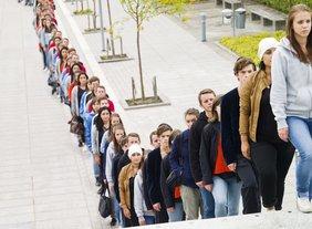 Eine lange Schlange von Menschen steht von weit hinten links bis vorne rechts; die ersten stehen auf Stufen einer Treppe.