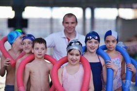 Kinder in Schwimmkleidung vor einem weiß gekleideten Trainer in einer Schwimmhalle.