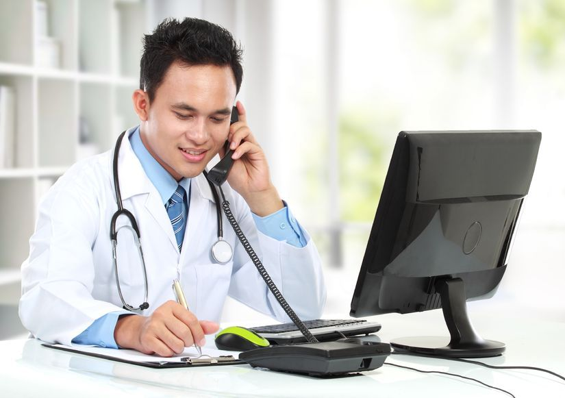 Arzt in weißem Kittel sitzt hinter einem Schreibtisch am Computer und telefoniert.