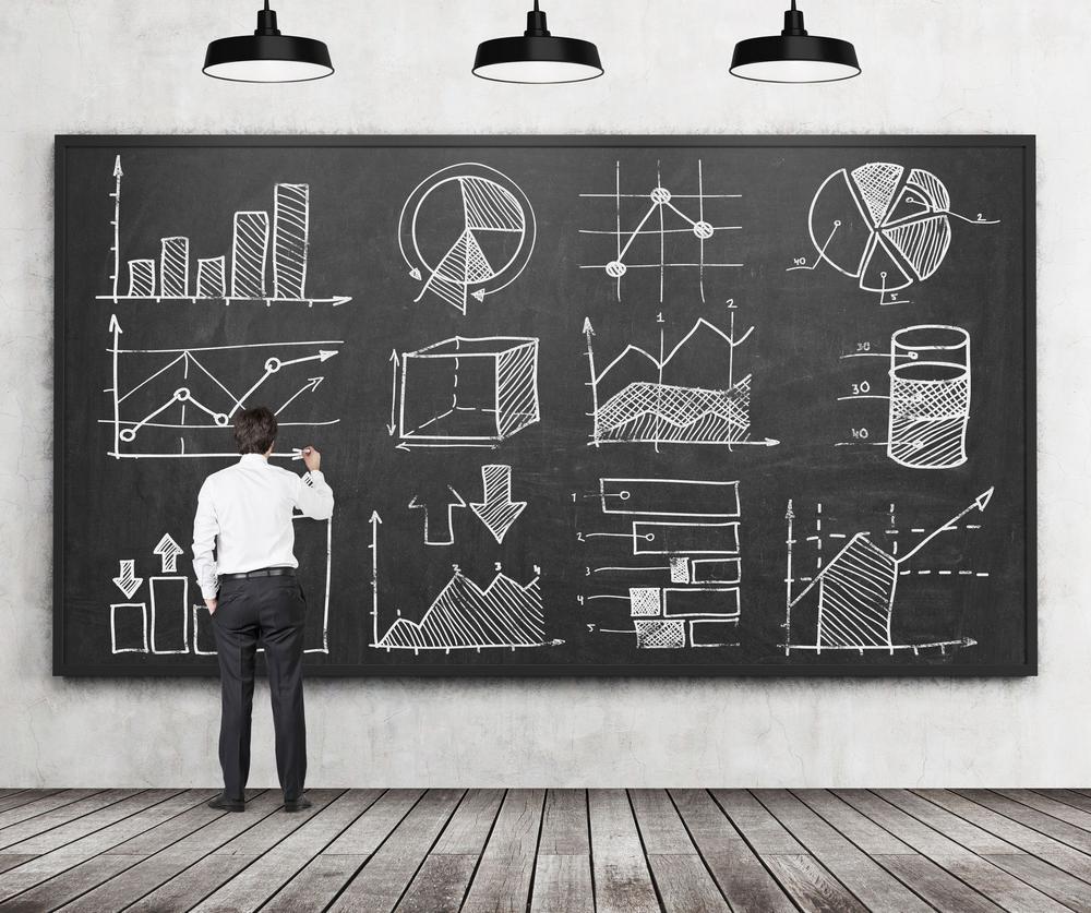 Ein Mann steht vor einer Tafel mit vielen Graphiken.