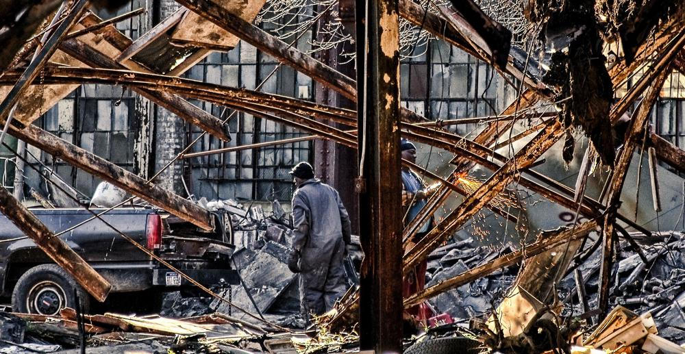 Abrissarbeiten in einer Stahlfabrik, zwei Arbeiter in Blaumännern schleifen Stahlträger auseinander.