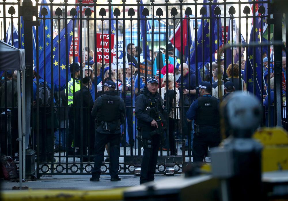 Protestierende mit Europa-Flaggen hinter einem von der Polizei bewachten Zaun.