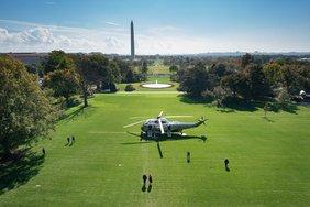 Donald Trump und Melania gehen auf den Hubschrauber zu, der auf einer grünen Wiese vor dem Weißen Haus steht. Über ihnen ein strahlend blauer Himmel.
