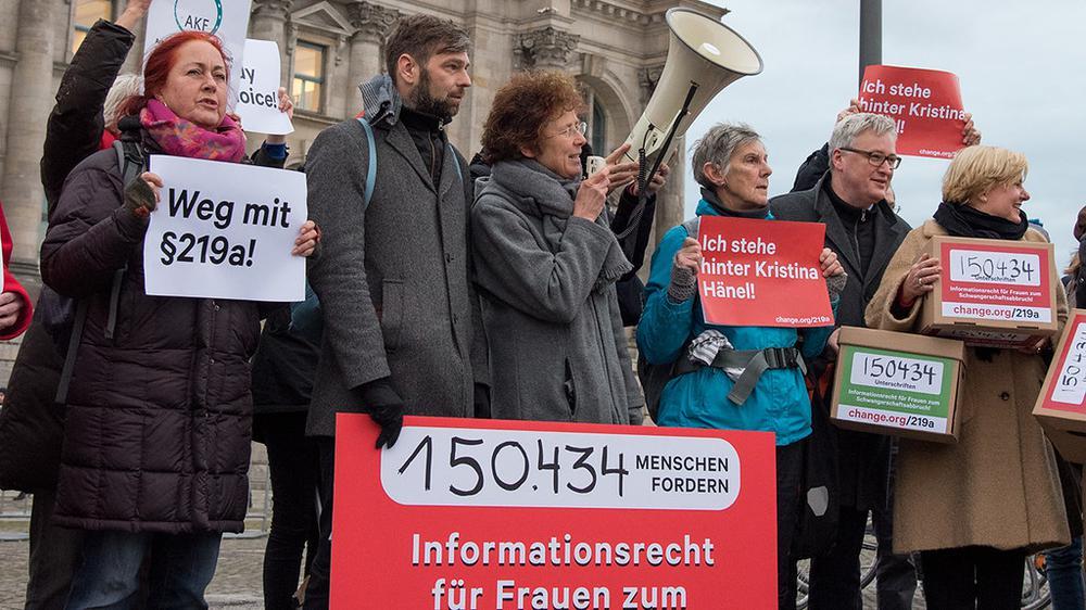Demonstrantinnen und Demonstranten halten Schilder hoch, auf denen steht: Weg mit dem § 219a.