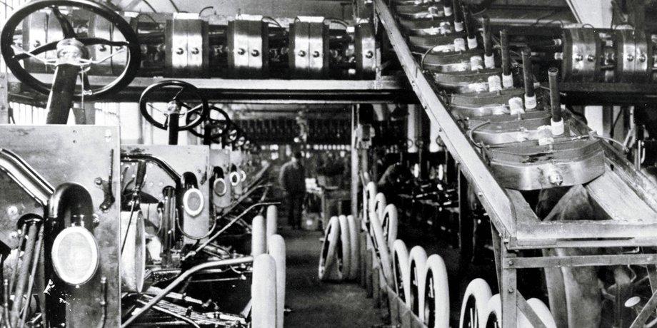 Fließbandproduktion bei Ford im Jahr 1913. Links Autos, rechts Reifen, die auf einem Band von oben herab transportiert werden.
