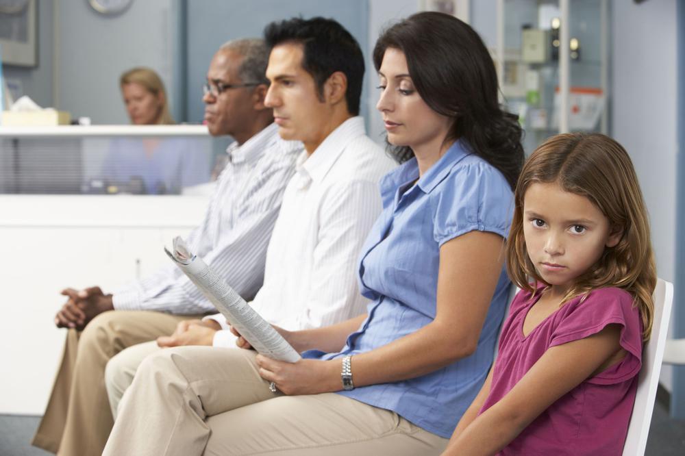 Vier Patienten - zwei Männer, eine Frau, ein Kind - sitzen in einer Reihe in einem Wartezimmer nebeneinander; im Hintergrund ist ein Rezeption mit Arzthelferin zu sehen.