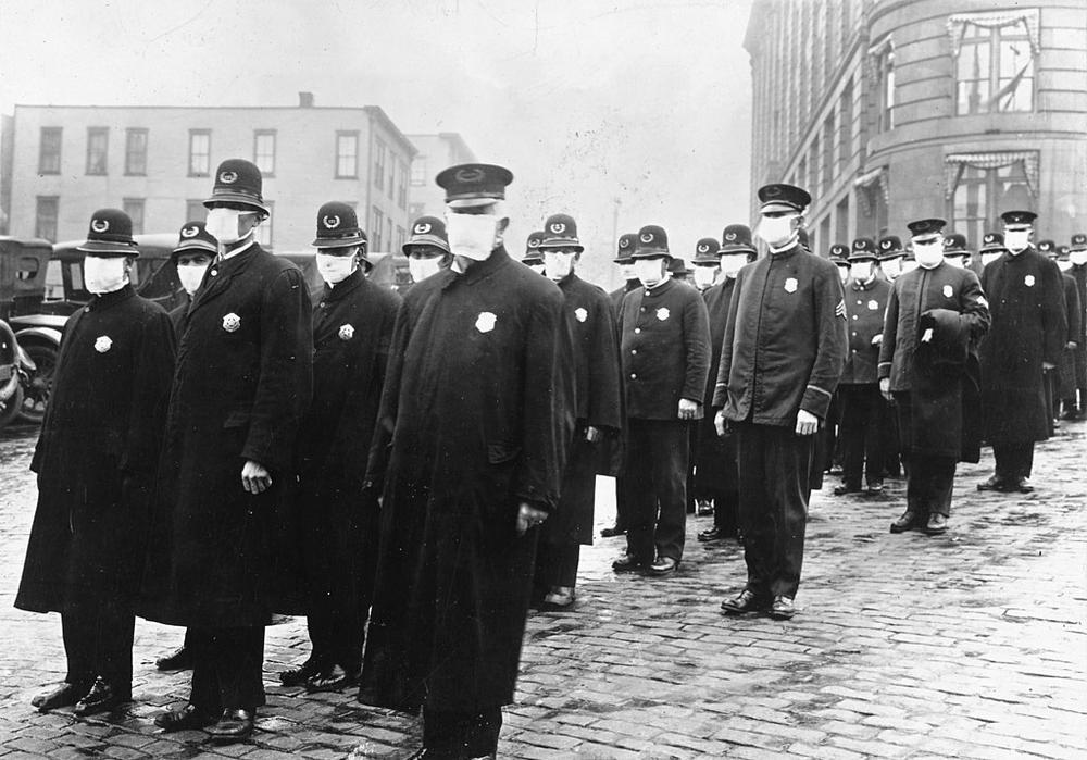 Schwarzweiß-Bild von Polizisten aus dem Jahr 1918, die alle Mundschutz tragen und in Formation eine Straße entlang laufen.