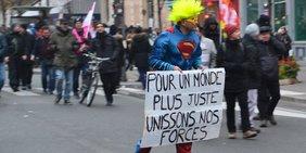 Ein als Superman gekleideter Mann auf Rollschuhen fährt vor Demonstranten mit Flaggen und hällt ein weißes Pappschild mit Text vor sich.