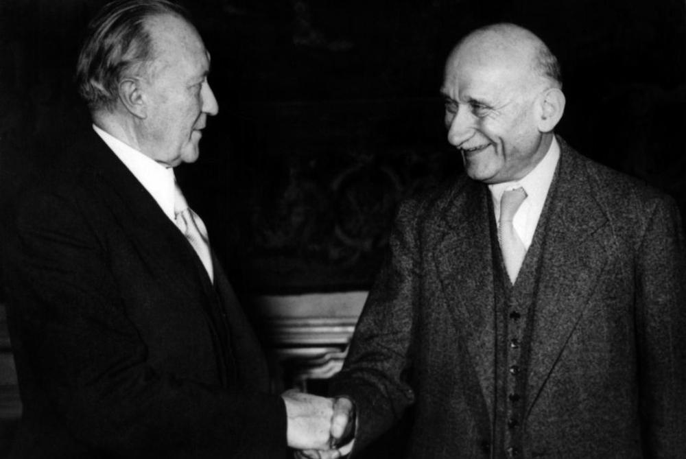 Konrad Adenauer und Robert Schuman geben sich die Hand. Schwarz-Weiß-Bild.