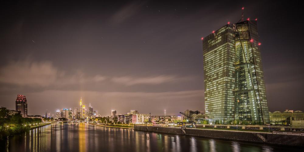 Skyline von Frankfurt am Main bei Nacht mit der Europäischen Zentralbank am rechten Ufer des Mains.