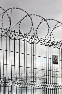 Zaun mit Stacheldraht oben drauf. Bild in Schwarzweiß.
