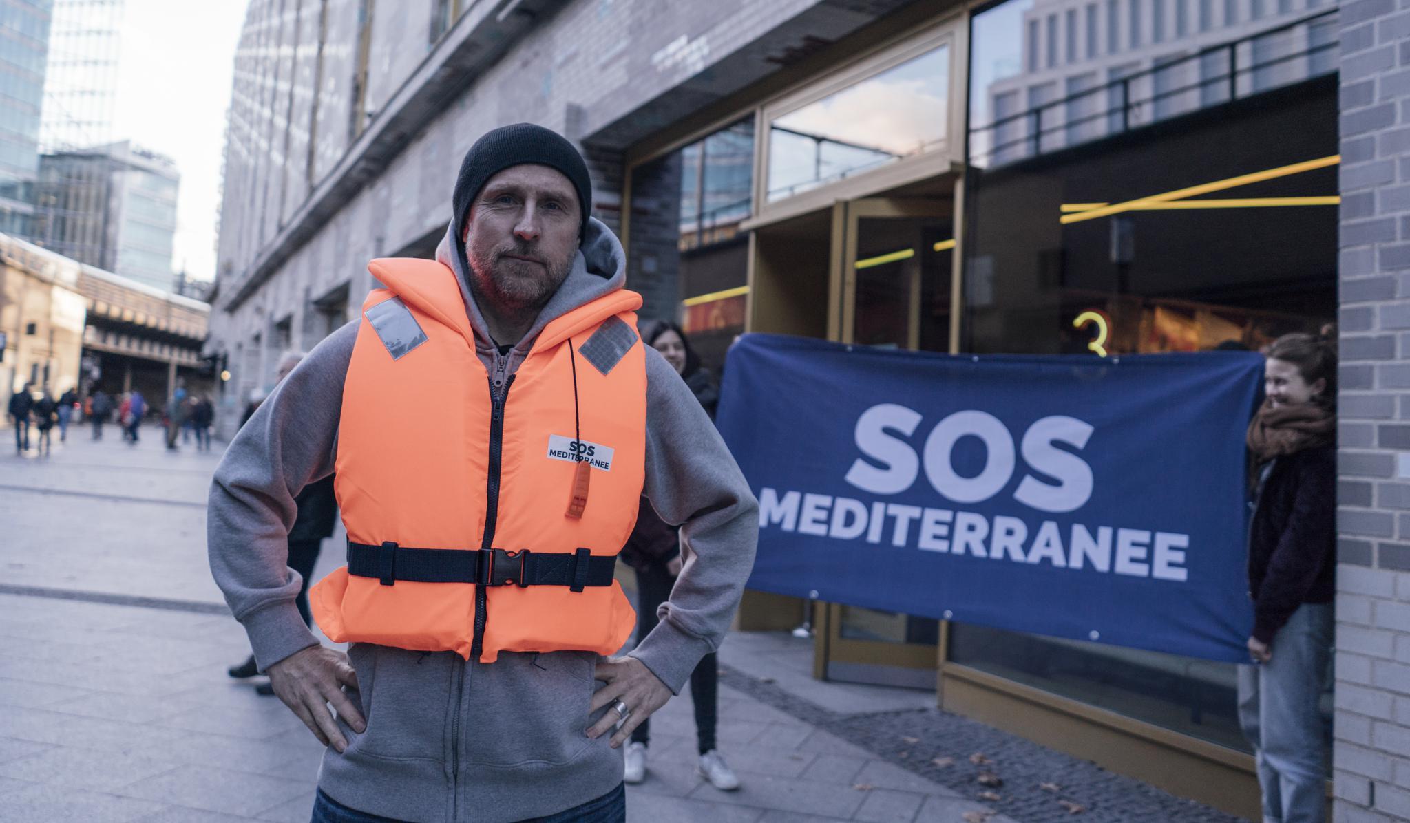 Der Schauspieler Bjarne Mädel in orangener Seerettungsweste vor einem Transparent von der Seerettungsorganisation SOS Mediteranee