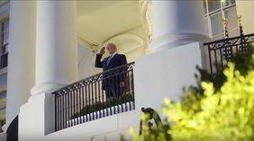 Donald Trump auf einem Balkon des Weißen Hauses salutiert. Er ist von schräg unten aufgenommen.