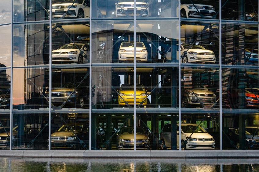 Autos stehen auf mehrern Etagen hinter einer Glasfassade.