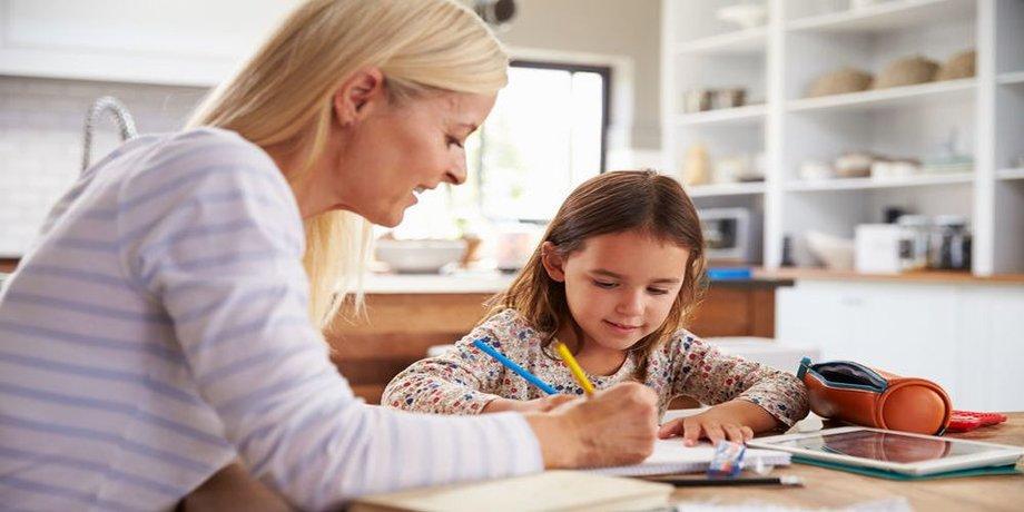Eine Mutter sitzt mit ihrer kleinen Tochter am Küchentisch und erklärt ihr etwas in einem Buch, das vor ihnen liegt.