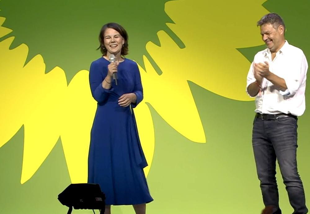 Eine Frau in einem blauen Kleid und ein Mann in Jeans und weißem Hemd stehen vor einer grünen Wand. Die Frau hält ein Mikrofon in der Hand.