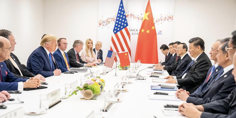 Donald Trump mit einer Delegation auf der linken Seite eines langen Tisches sitzt Xi Jinping und seiner Delegation gegenüber. Im Hintergrund eine US-amerikanische und eine chinesische Fahne.