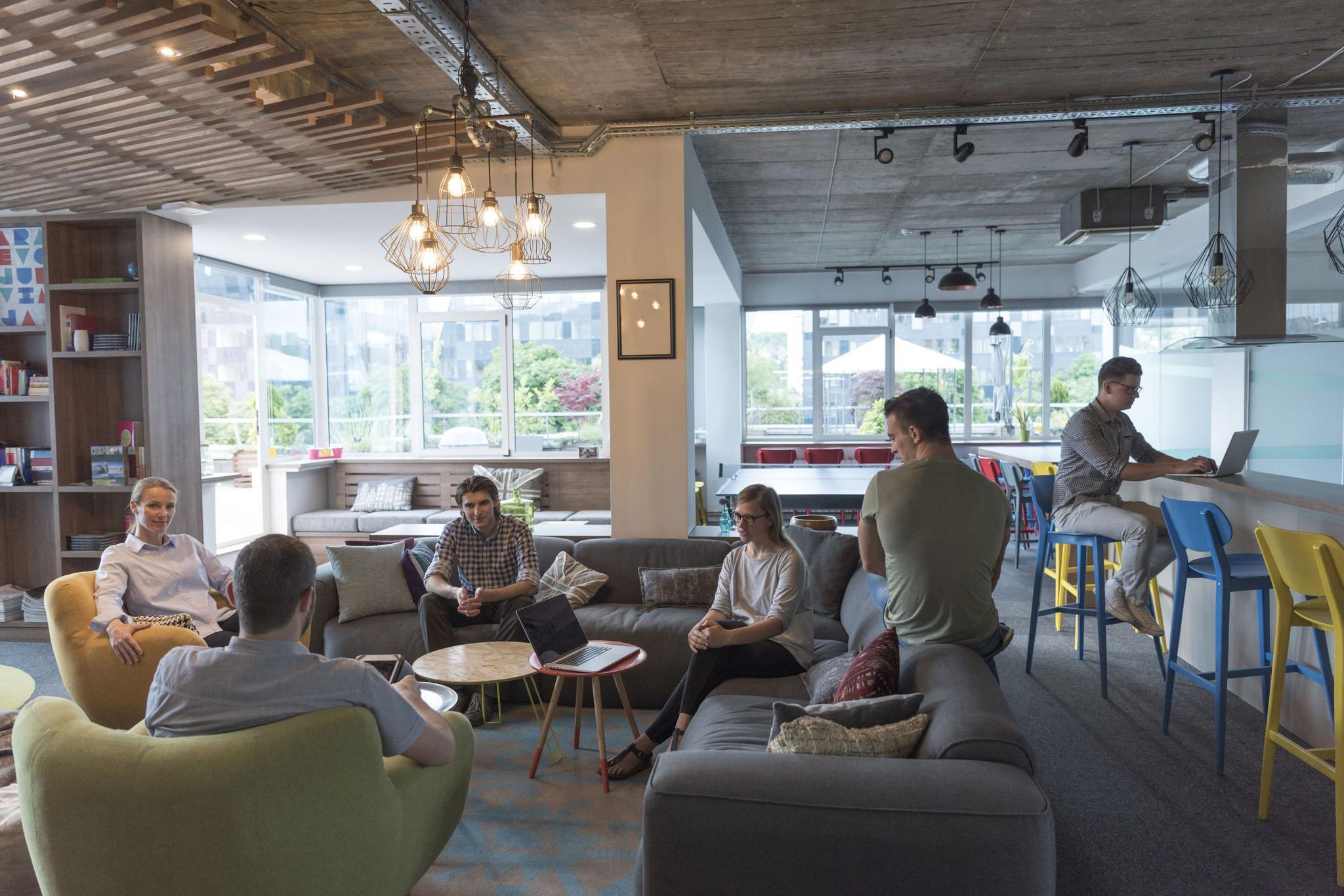 Modernes Großraumbüros, in dem die Angestellten in der Mitte auf Sesseln und einem Sofa sich gegenüber sitzen. Rechts im Hintergrund stehen Arbeitstische.