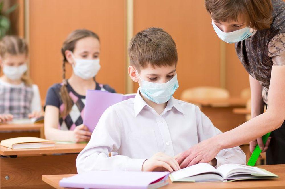 Grundschüler sitzen einzeln an Tischen hintereinander und tragen Atemschutzmasken. Eine Lehrerin, auch mit Maske, zeigt dem Schüler in der ersten Reihe etwas in seinem Buch.