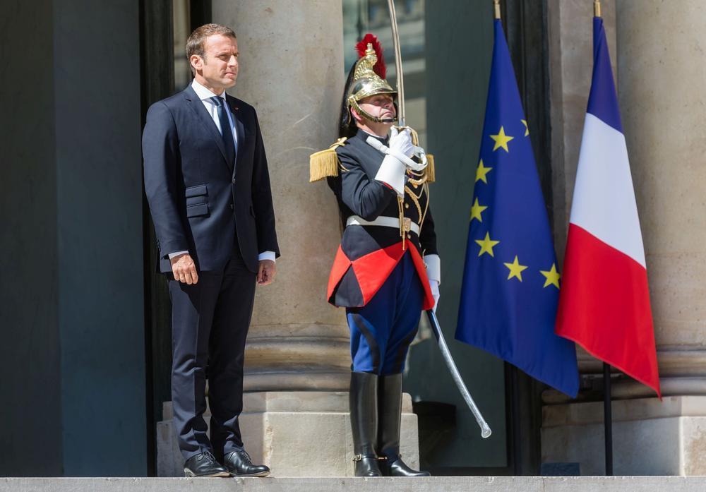 Emmanuel Macron steht mit einem Soldaten vor der europäischen und französischen Flagge