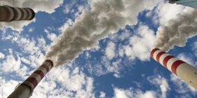 Kraftwerksschornsteine stoßen Rauch in einen blauen Himmel mit weißen Wolken aus.