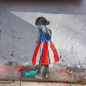Wandbild von einem Mädchen in einem Kleid mit Muster der US-Flagge. Sie blickt auf eine kleine Freiheitsstatue, die auf dem Boden liegt.