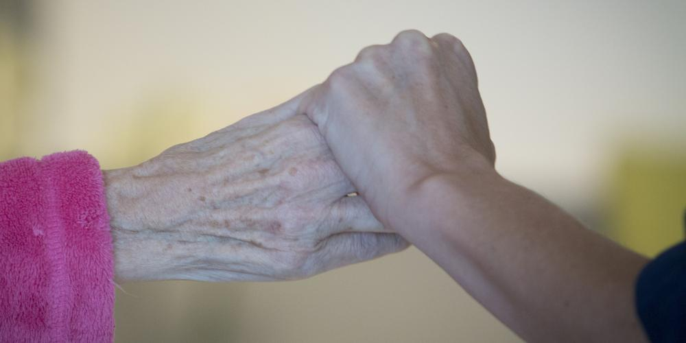 Die Hand eines jüngeren Menschen hält die Hand eines Älteren.