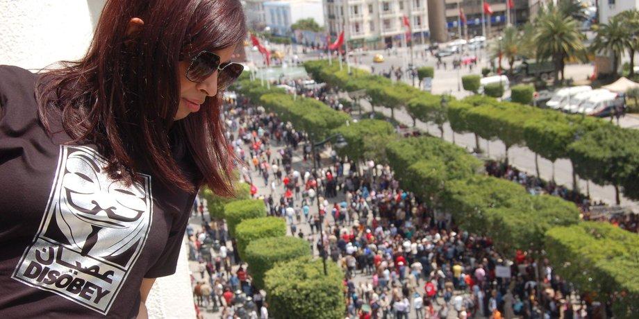 Eine Frau mit langen brünetten Haarten und einer Sonnenbrille blickt auf eine Straße, auf der Tausende Menschen entlangziehen.