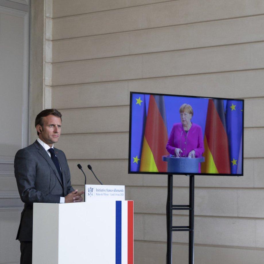 Emmanuel Macron steht an einem Rednerpult mit französischer Flagge an der rechten Seite. Angela Merkel ist, ebenfalls hinter einem Pult, auf einem Bildschirm zu sehen. Hinter ihr die deutsche Flagge.