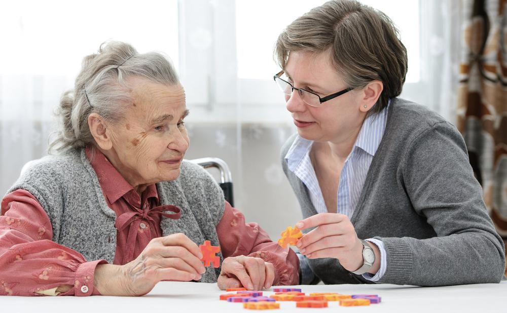 Eine alte Frau legt mit einer jüngeren Frau ein Puzzle in einem Altersheim