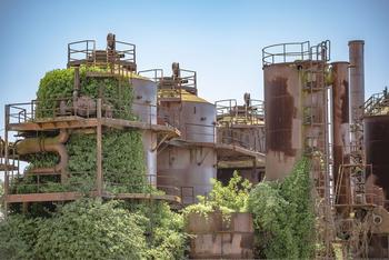 Stillgelegte Industrienanlage, die halb von Bäumen und Büschen überwachsen ist.