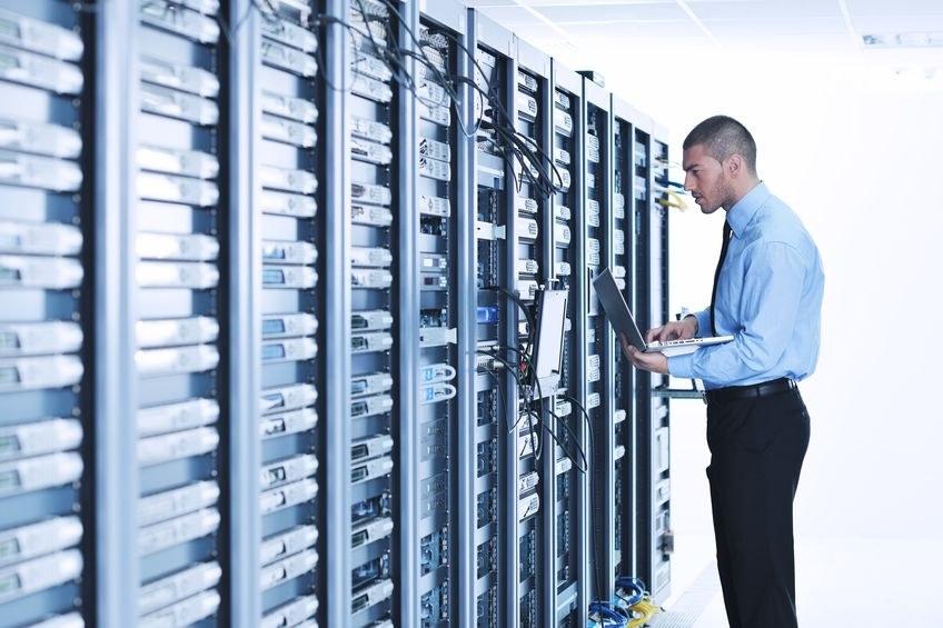 Großer Computerserver, vor dem ein Mann mit Laptop steht und etwas überprüft.