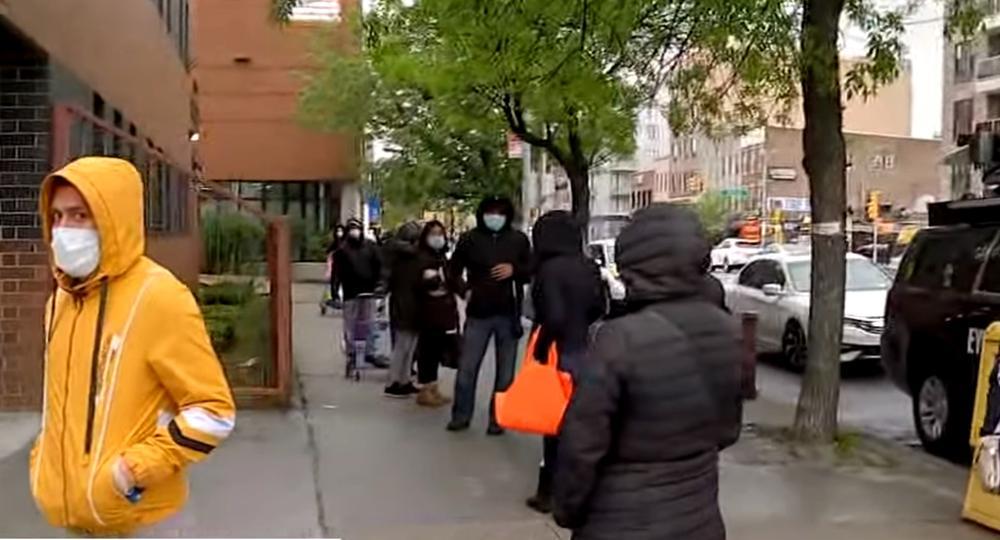 Schlange von Menschen in dunklen Jacken, die auf der Straße anstehen.