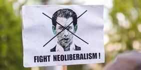 """Ein Pappplakat an einem Holzstock, auf dem schemenhaft Sebastian Kurz abgebildtet ist, darunter die Forderung """"Fight Neoliberalism""""."""