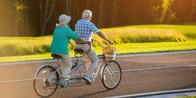 Rentner fahren auf einem Tandem im Sonnenschein auf der Straße.