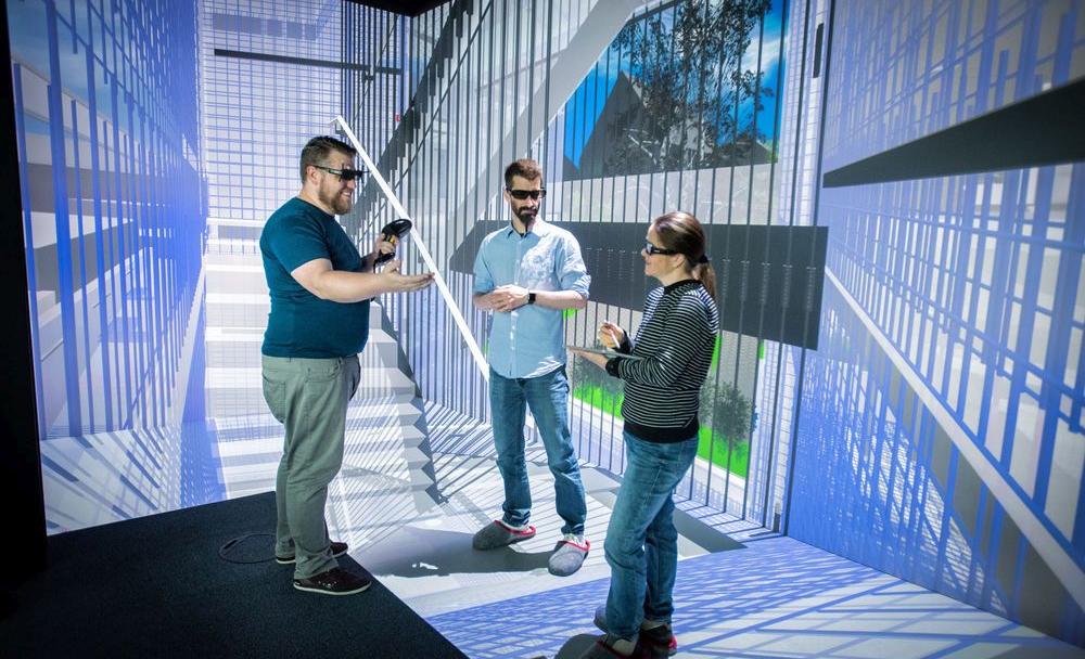 Drei Personen stehen in einem virtuellen Raum, der ein Treppenhaus andeutet.