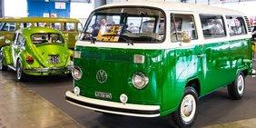 VW Käfer und Bulli in einer Halle.