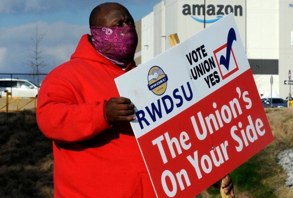 Ein schwarzer Prostierer hält vor dem Amazon-Gebäude ein Schild hoch, dass für die Gewerkschaft wirbt.