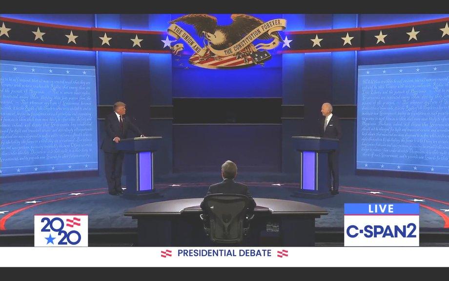 Bühne mit blauem Boden, auf der zwei Pulte rechts und links stehen, dahinter die Präsidentschaftskandidaten. Vor der Bühne ein Moderator an einen halbrunden Tisch, der nur von hinten zu sehen ist.