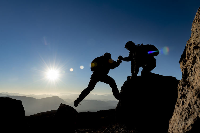 Bergwanderer helfen einander beim Steigen auf einen Felsen. Aufnahme im Gegenlicht