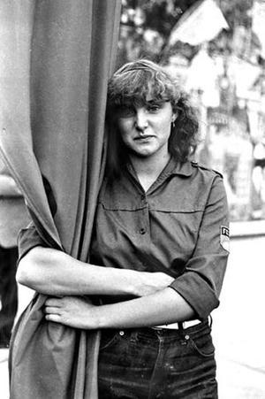 Mädchen in FDJ-Uniform, die eine Fahne umarmt. Aufgenommen 1982 in Potsdam.