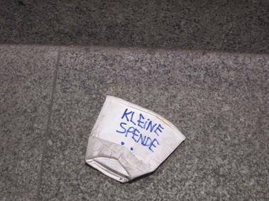 Zerknüllter Pappbecker auf dem Boden mit der Aufschrift Kleine Spende.