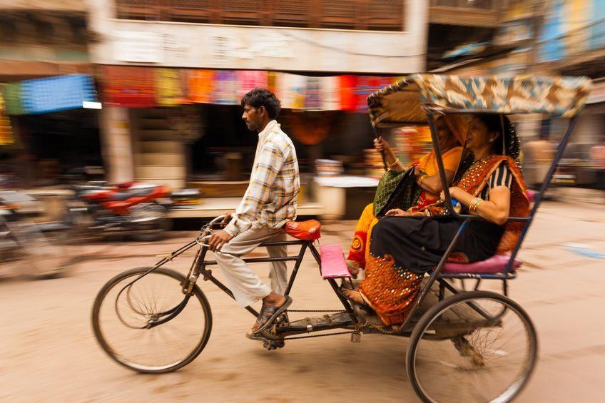 Eine Fahrrad-Rikschaf mit einem Fahrer und zwei Frauen im Fonds fährt auf einer Straße.