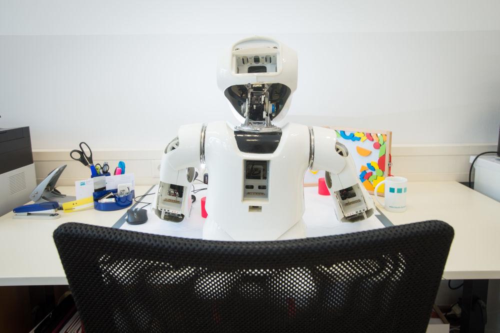 Ein Roboter sitzt an einem Schreibtisch, aufgenommen von hinten.