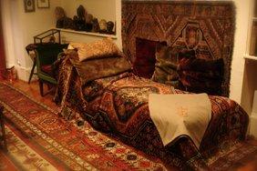 Ein Kanapee mit einem rötlichen Teppich, an der Wand hängt ein ähnlicher Teppich.
