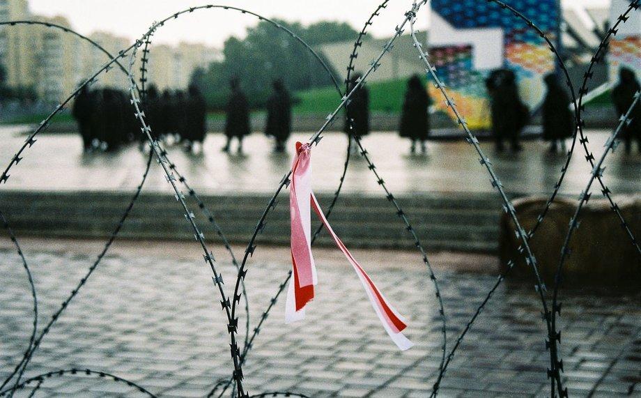 Stacheldraht sehr nah mit einer kleinen Schleife darin in Rot-Weiß, den belarussischen Nationalfarben. Im Hintergrund sind dunkel gekleidete Figuren unscharf zu erkennen, vermutlich Soldaten.