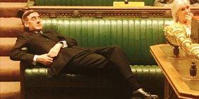 Jacob Reese-Mogg liegt halb auf einer Bank im Unterhaus und scheint ein Nickerchen zu machen.