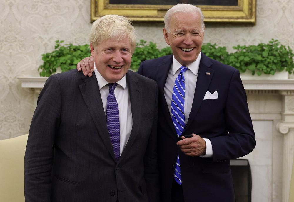 Zwei Männer stehen nebeneinander und lächeln. Der Ältere hat dem Jüngeren die Hand auf die Schulter gelegt.